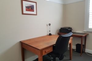 The dedicated office space in Veda House featuring two desks and a high capacity printer.